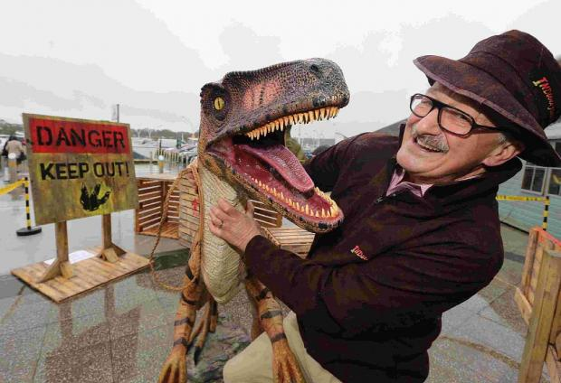 ROAR: Peter Matthews, Castlepoint Centre manager, gets to grips with one of the life-sized dinosaurs