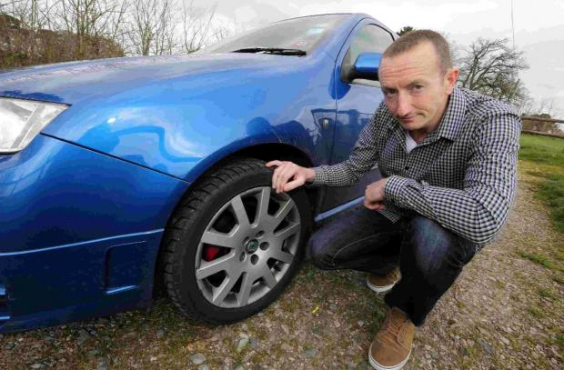 DAMAGE: James Fletcher with his car damaged by a pothole