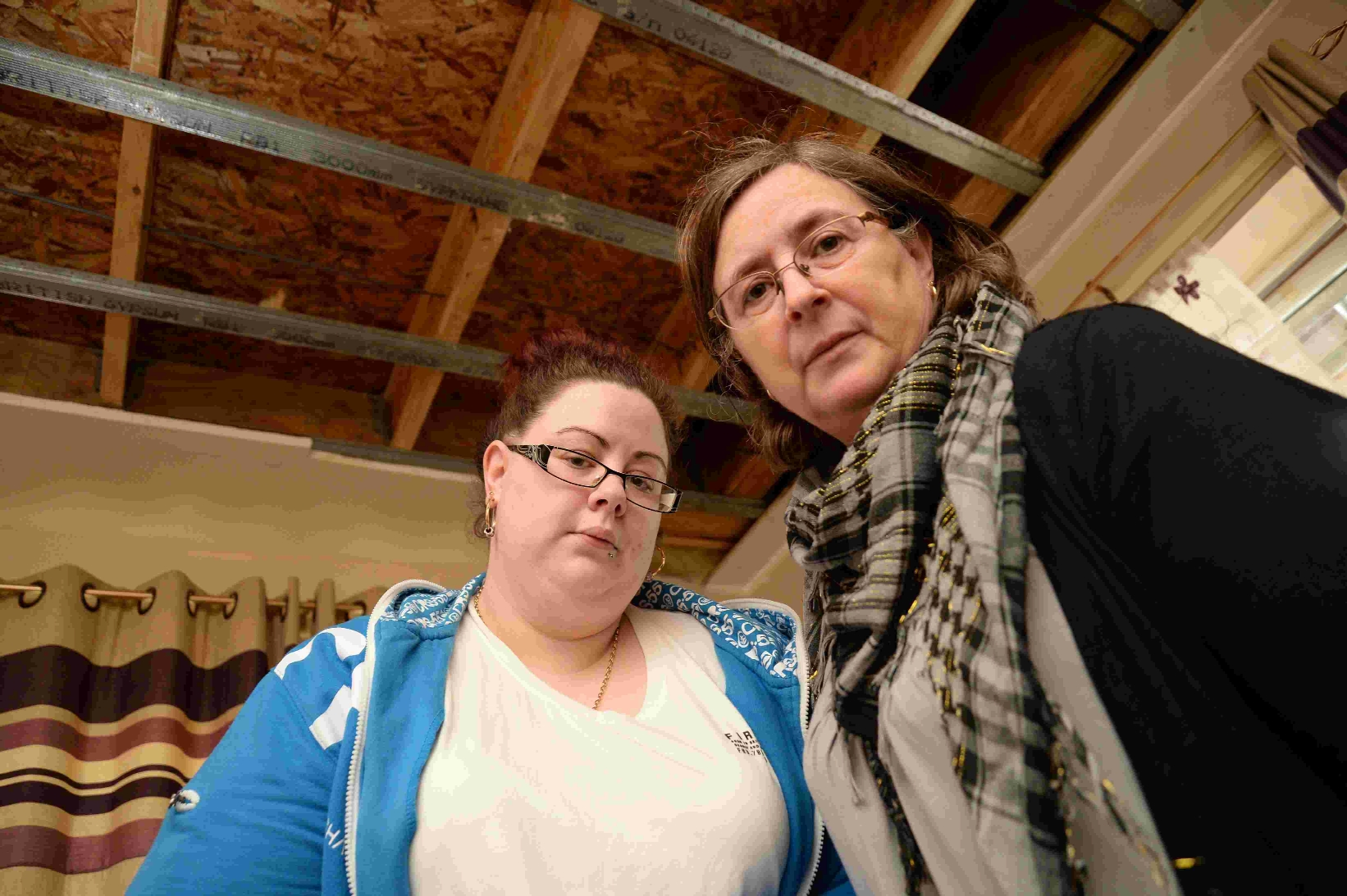 Karen Carr and her daughter Emma-Jane below  a damp ceiling