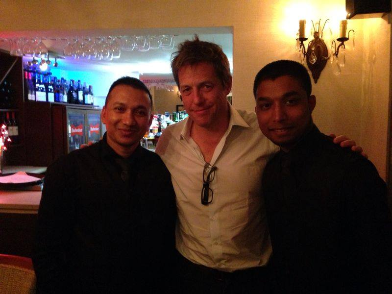 Hugh Grant with staff at the Masala Bay restaurant in Christchurch