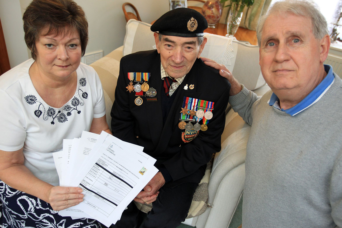 TRIPLICATE: D-Day veteran Ted Young with daughter Irene Richards, son-in-law Paul and the sheets of paperwork
