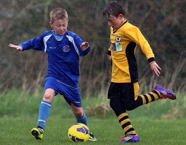 TIGHT TUSSLE: Action from Branksome's win over West Moors (blue)