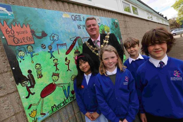 Mayor of Poole Phil Eades unveils the mural at Branksome Recreation Ground in Poole alongside students from Heatherlands School