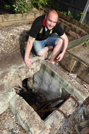 SURPRISE FIND: Steve Saywell with the WW2 air raid shelter that he has uncovered in the back garden of  his Ensbury Park home