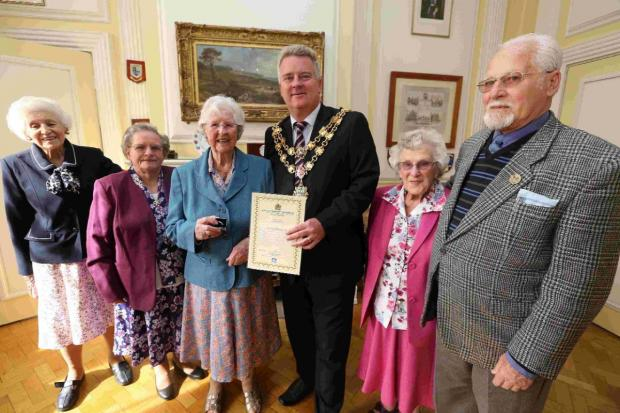 PROUD MOMENT: Mayor of Poole Cllr Phil Eades awards Margaret Bailey, centre left, with the Poole Gold Award. Pictured with the Autumn Club Committee
