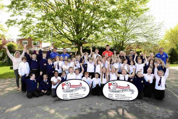 Bournemouth star Elliott Ward with youngsters from Kingsleigh Primary School