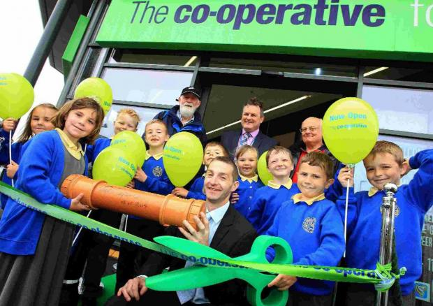 CUTTING EDGE: Pupils from Twin Sails Infant School join Co-op manager Simon Carpenter, front centre, at the official opening of the new store in Blandford Road, Hamworthy