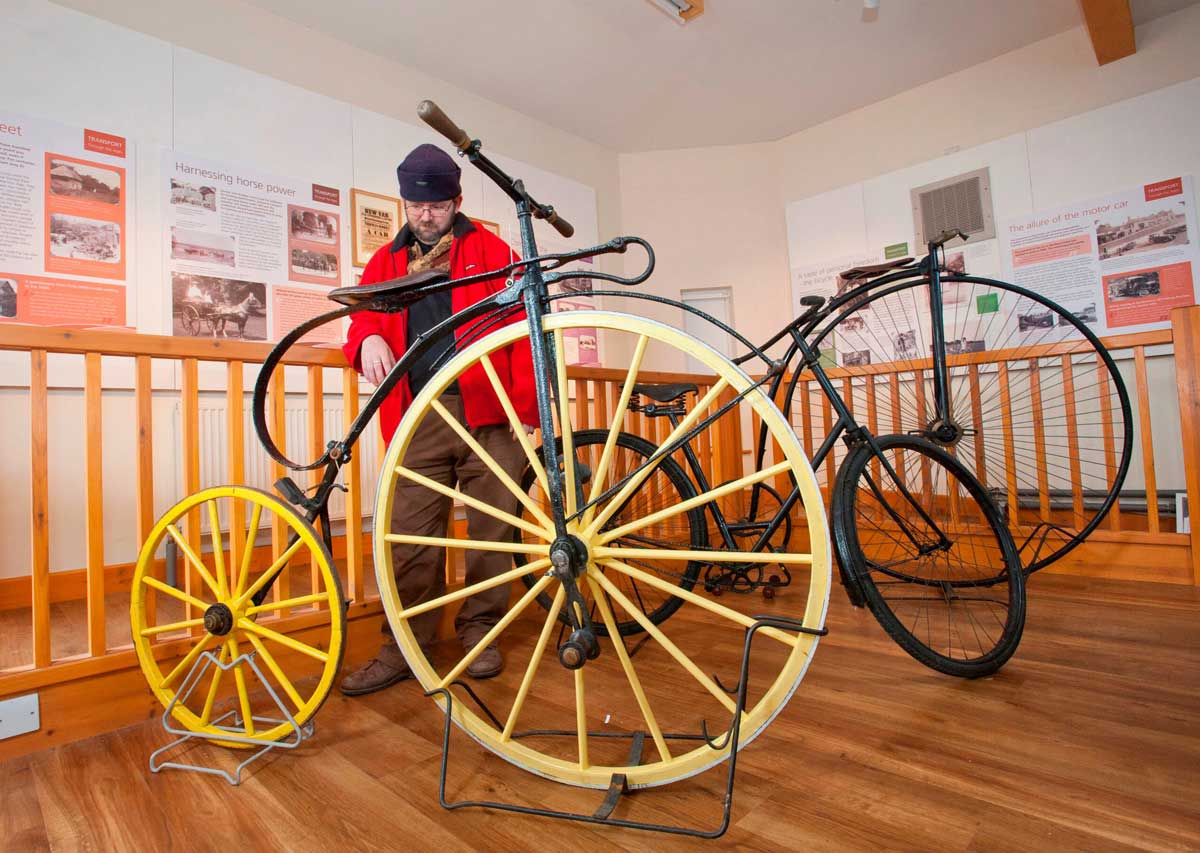 A trio of antique bikes at the exhibition – the yellow wheeled velocipede or boneshaker, a safety bicycle and a penny farthing