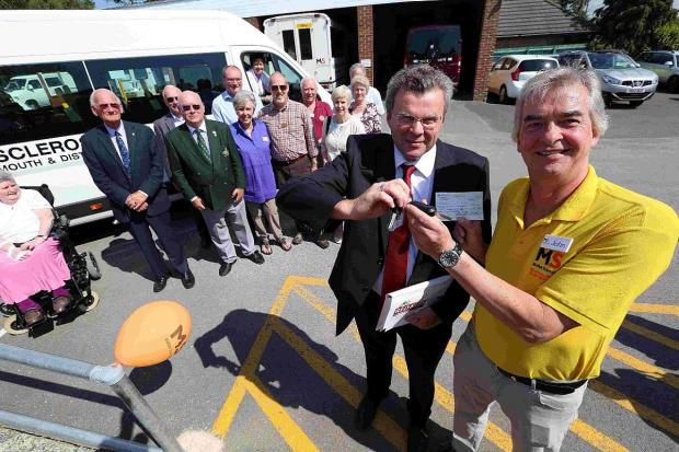 LIFELINE: Used vehicle sales manager Steve Newby hands keys for a brand new minibus to John Astley with fundraisers, volunteers and facility users