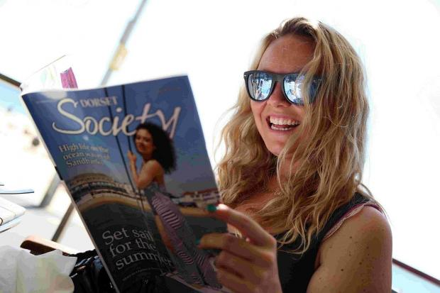 HOLIDAY: Charlie Brooks enjoys a copy of Dorset Society in shade from the sun at West Beach near to Bournemouth Pier