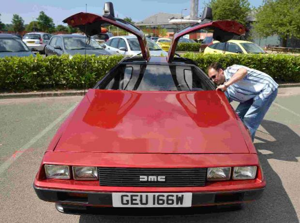 Bournemouth Echo: ON SHOW: Matt Woodhall inspects a rare red painted DeLorean