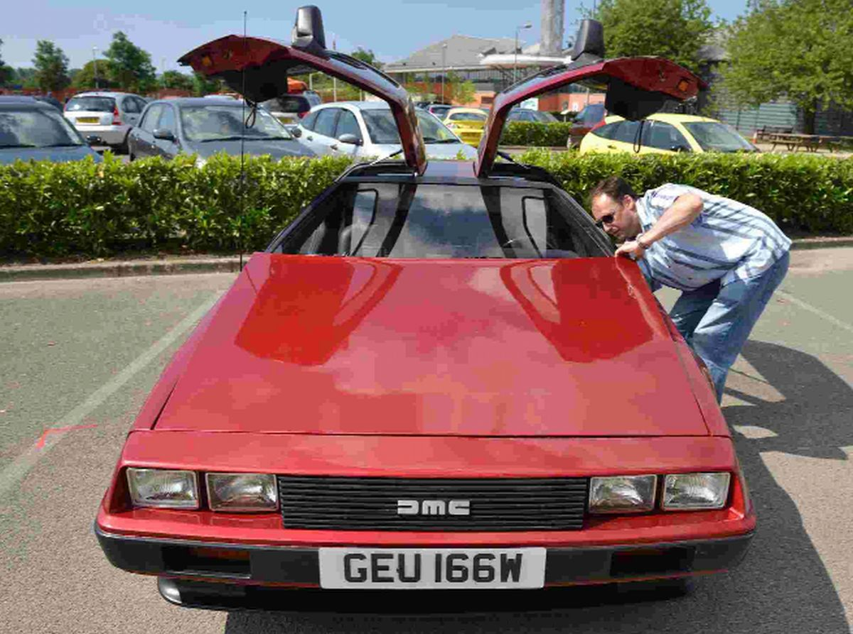 ON SHOW: Matt Woodhall inspects a rare red painted DeLorean