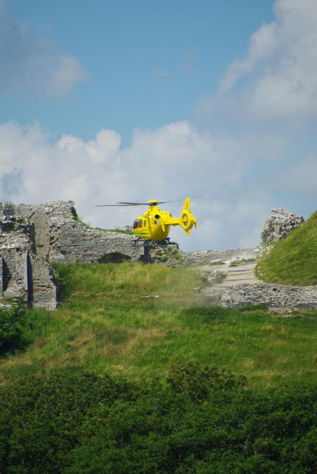 Bournemouth Echo: The Air Ambulance lands at Corfe Castle. PIc by Martin Yirrell