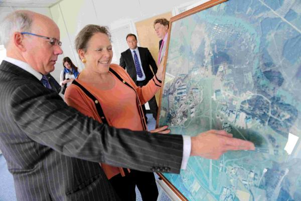 Manchester Airports Group planning director John Twigg and Baroness Kramer survey an aerial photograph of the airport site to discuss how a new multimillion pound investment will be spent