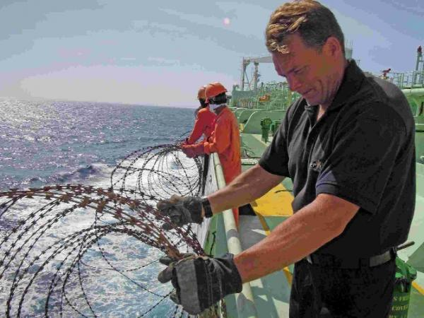 A maritime security worker fixes razor wire to sides of ship to deter pirates