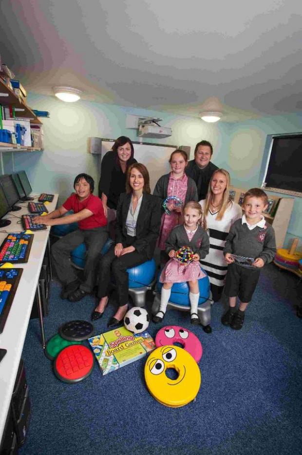 Bournemouth Echo: KIND DONATION: JP Morgan's Catherine McDonald, seated, with assistant headteacher Scott Tait, Aimee Rutherford, back right, and Lizzie Sharpe, right, alongside pupils