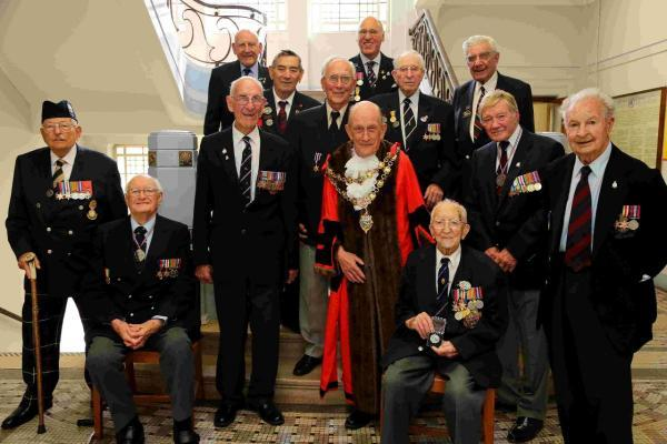 The Mayor of Poole Cllr Peter Adams presents medals to Normandy veterans who were unable attend the D-Day commemorations on June 6 in France