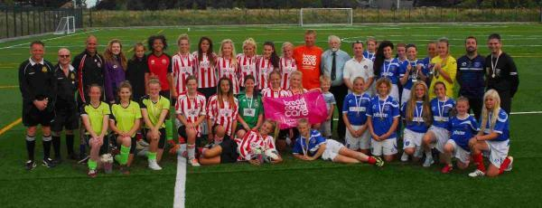 Female footballers battle it out on the pitch to raise money for cancer charity