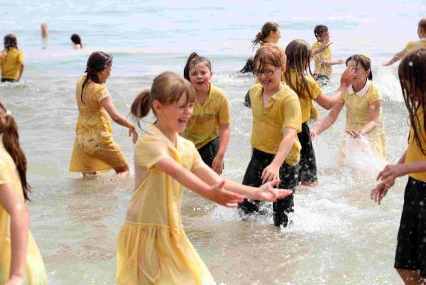 St Mark's Primary School pupils celebrate the start of their summer holidays by running into the sea at Alum Chine in their uniforms