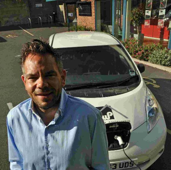 Steve Wells with DWP Housing Partnership's electric car that is charged with electricity captured by the solar panels on the roof