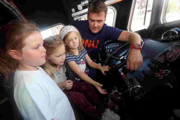 AT THE HELM: Lauren and Freya Squibb, with Tia O'Connell-Davidson, are shown the controls to an RNLI lifeboat, by Deputy 2nd Cox Glen Mallen at the RNLI open day on Poole Quay