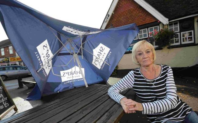 Landlady Lynne Baldwin with the wrecked shelter at Gulliver's
