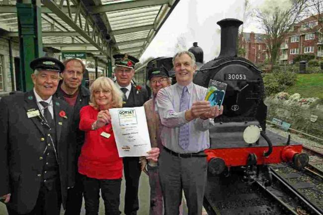 CHUFFED: Richard Jones, general manager of Swanage Railway, with volunteers and staff holding their certificate and trophy