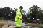LITTER: A council worker clears up the mess left by travellers at the Creekmoor park and ride site