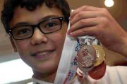 HIGH HOPES: Lewis Brimble, 14, with his many medals