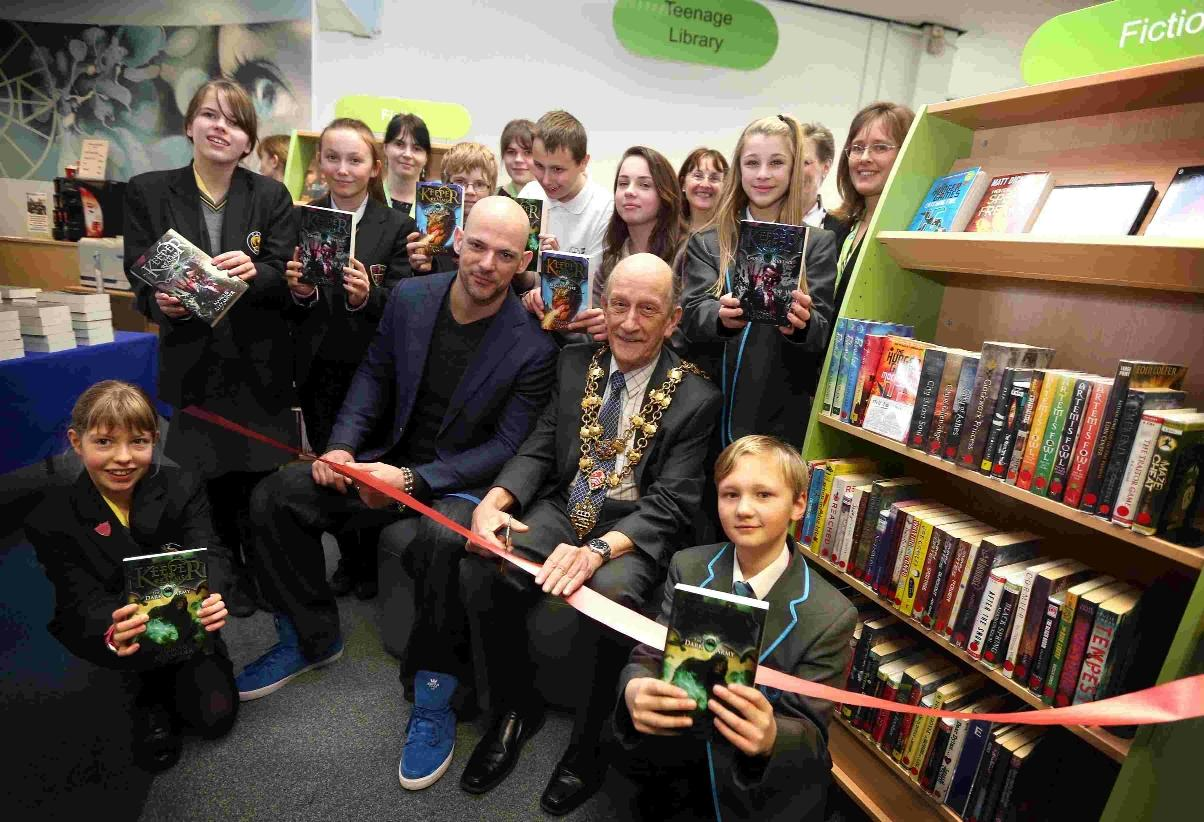 Author Marcus Alexander and Mayor of Poole Councillor Peter Adams, centre, are joined by children from five schools across Poole in the new teenage library