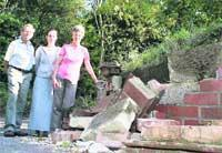 INSPECTING THE DAMAGE: Trevor and Irene Selway with their daughter Elizabeth in the driveway of their Merley home where a bus struck a wall
