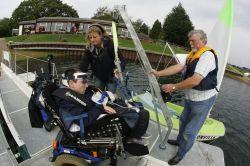 LAUNCHING HISTORY: Keith Harris is helped into the dinghy, which he controls with his tongue, by his carer Helen Griffiths and Mike Golden from Sailability