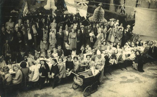 VE Day party in Woking Road, Parkstone, sent in by Doreen Bennett ( nee Alcock ). She is the small girl with dark hair directly behind the child in the pram.'Granny Young'  is the lady pushing the pram. Picture taken from an upstairs window.