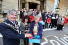 Mayor of Bournemouth Cllr. John Adams buys the first poppy from Cllr. Anne Rey at the Town Hall with Mayoress, Suzi Thornton-Vanzi, veterans and other members of the council.