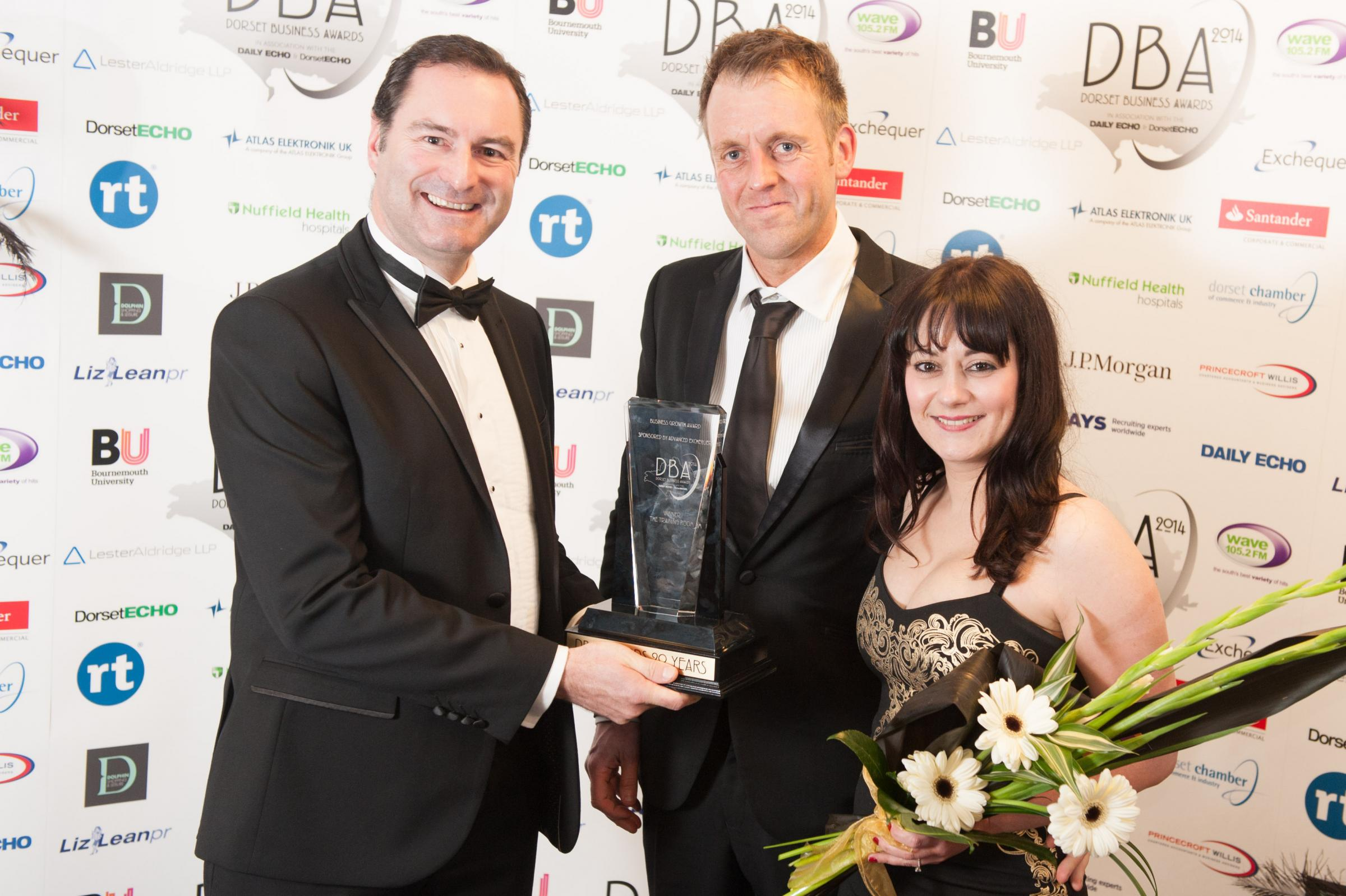 WINNERS: L-r, Greg Ford of Advanced Exchequer presents a Dorset Business Award to Jonathan Davies and Hayley Evans of the Training Room in 2014