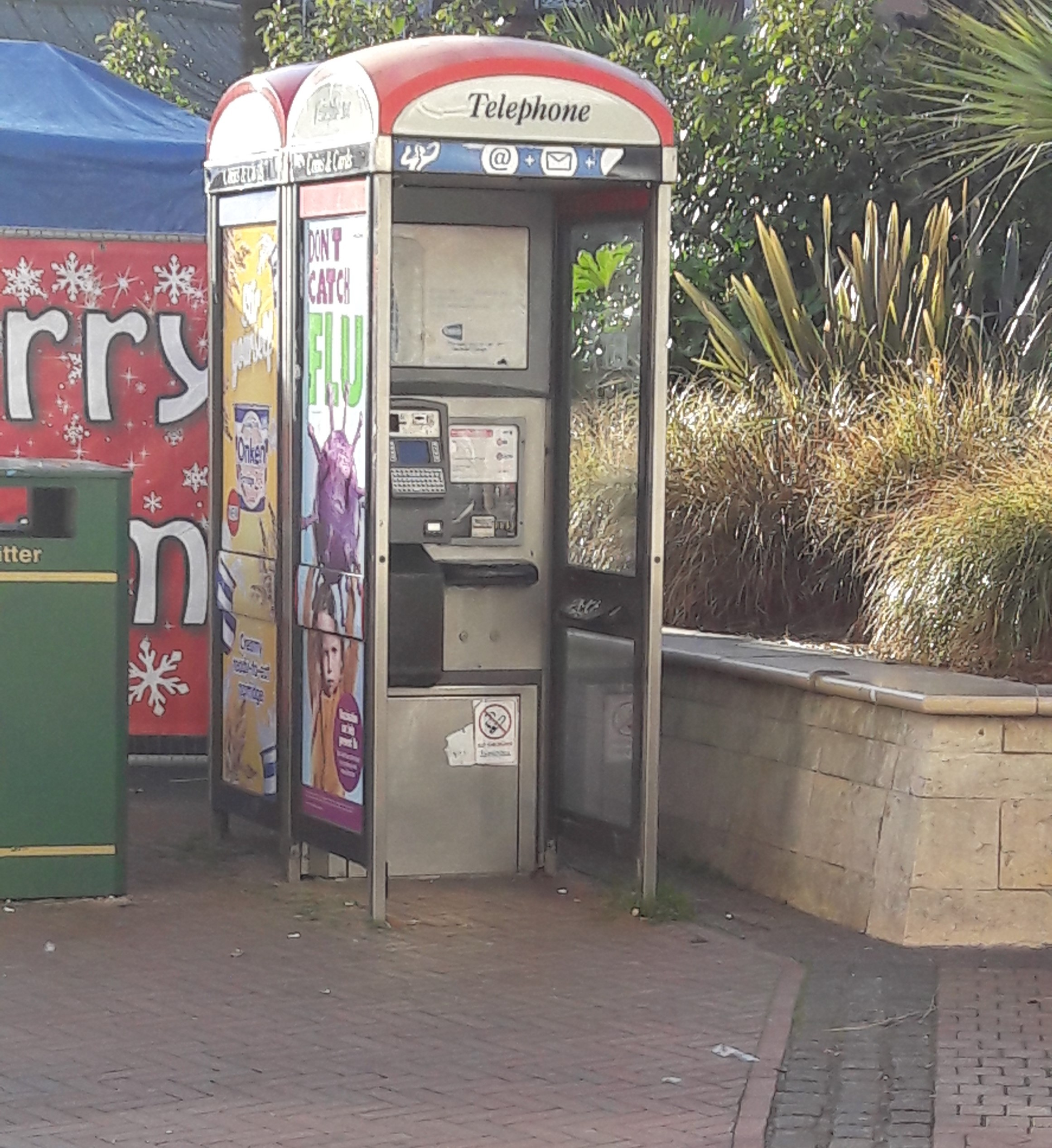 A phone box with a door missing at Bournemouth Square