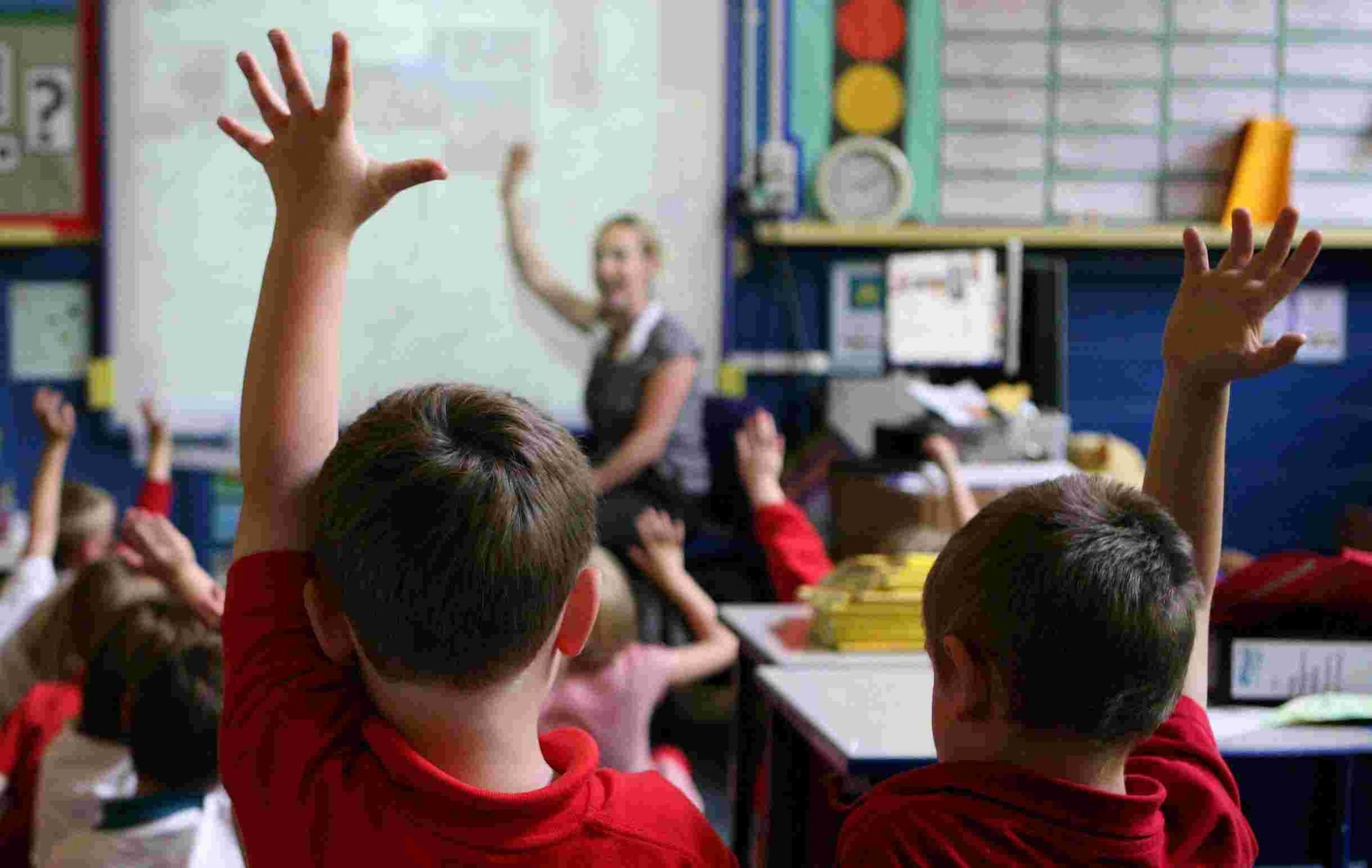 "Embargoed to 0001 Monday March 16..File photo dated 06/07/11 of children at school raising their hands to answer a question as schools are facing a ""postcode lottery"" in funding, with some likely to receive almost £2 million less th"