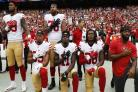 San Francisco 49ers players kneel during the American national anthem