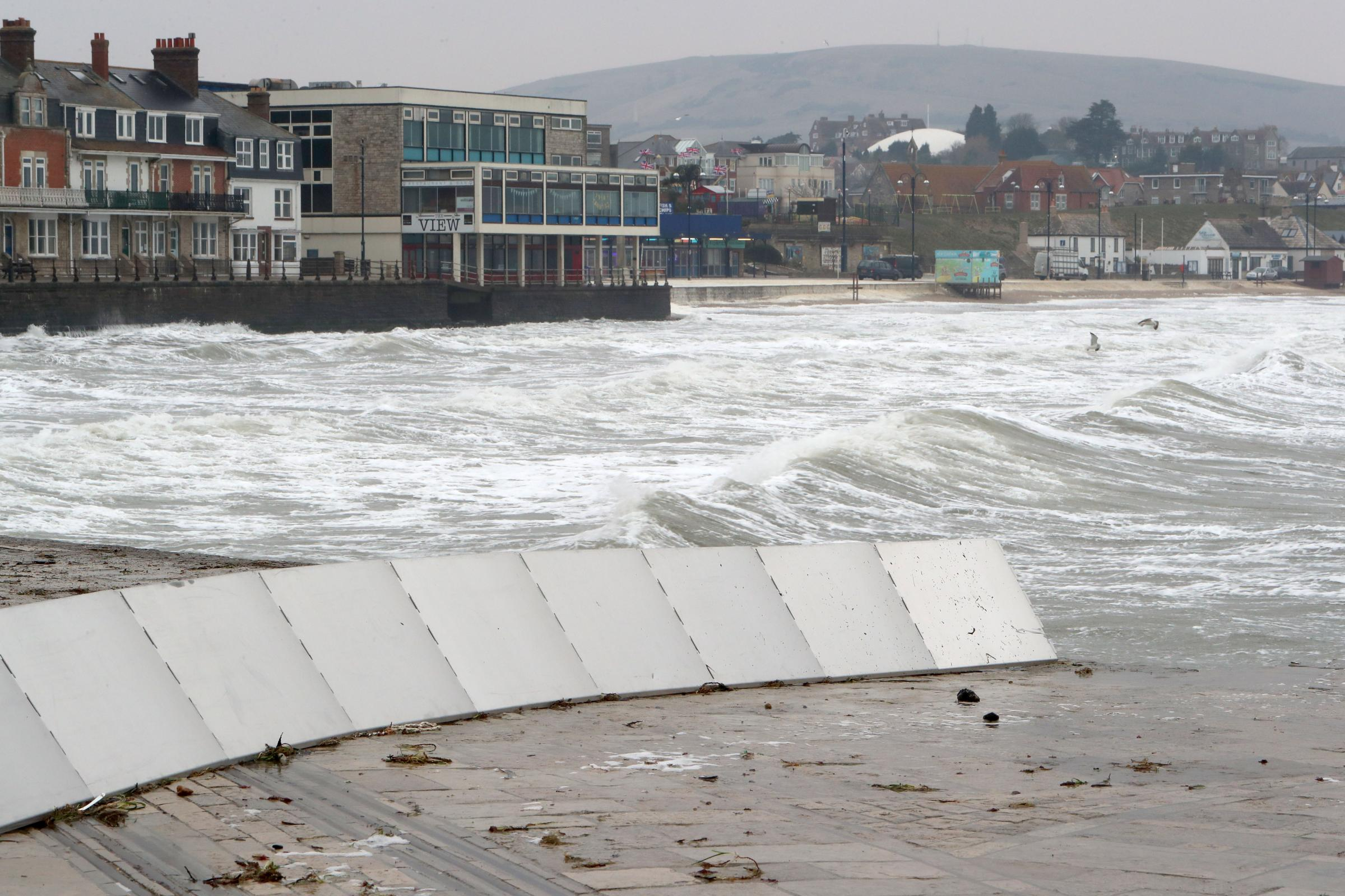 Snow settles over Dorset on Thrusday morning. .Heavy seas at Swanage but very little snow. .The flood defence barrier in place. ..