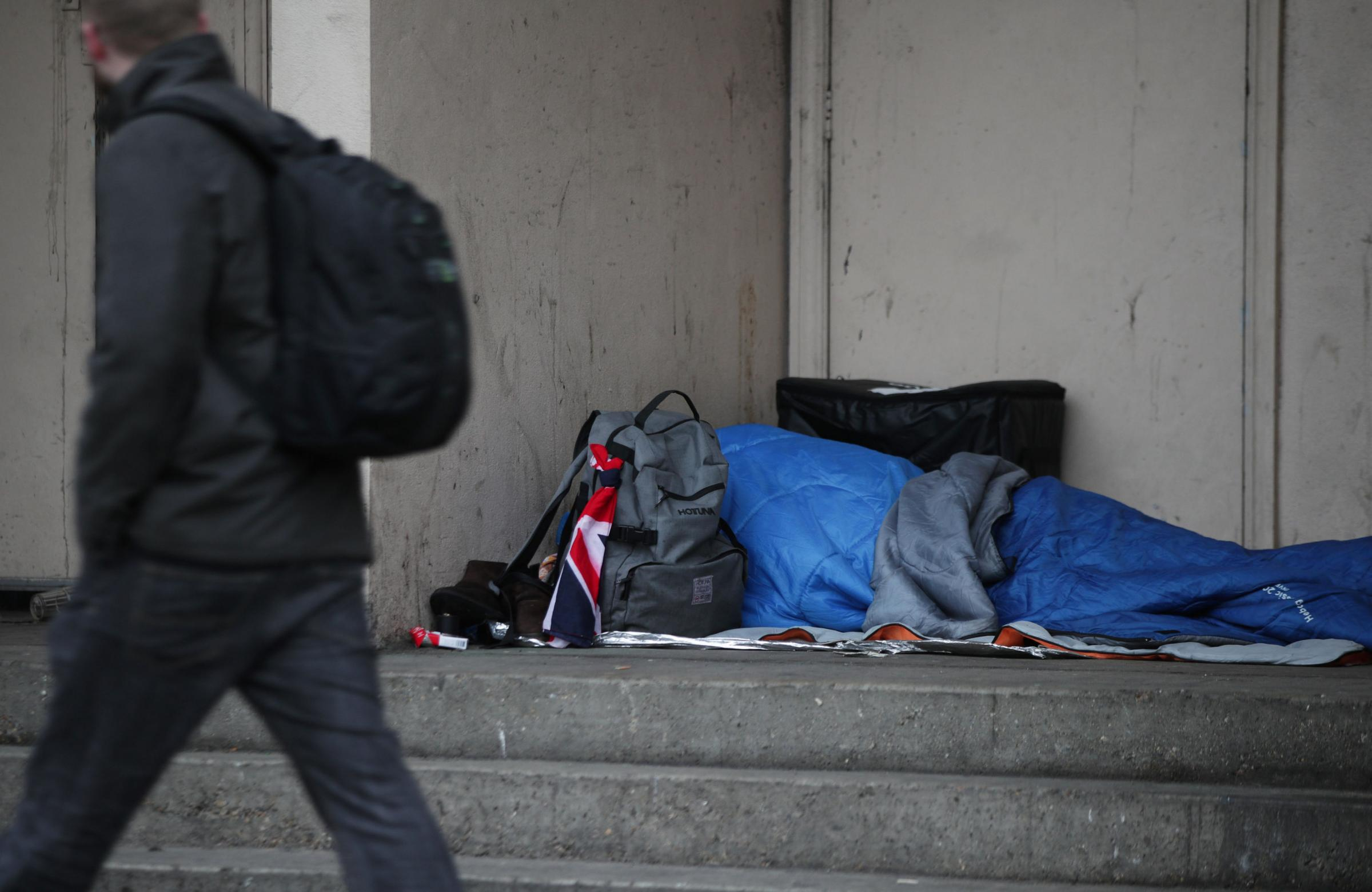 HELPING : A person sleeping rough in a doorway