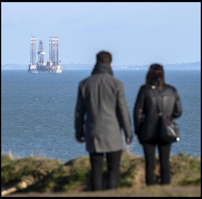 Sightseers at Old Harry Rocks looking at the controversial oil drilling platform