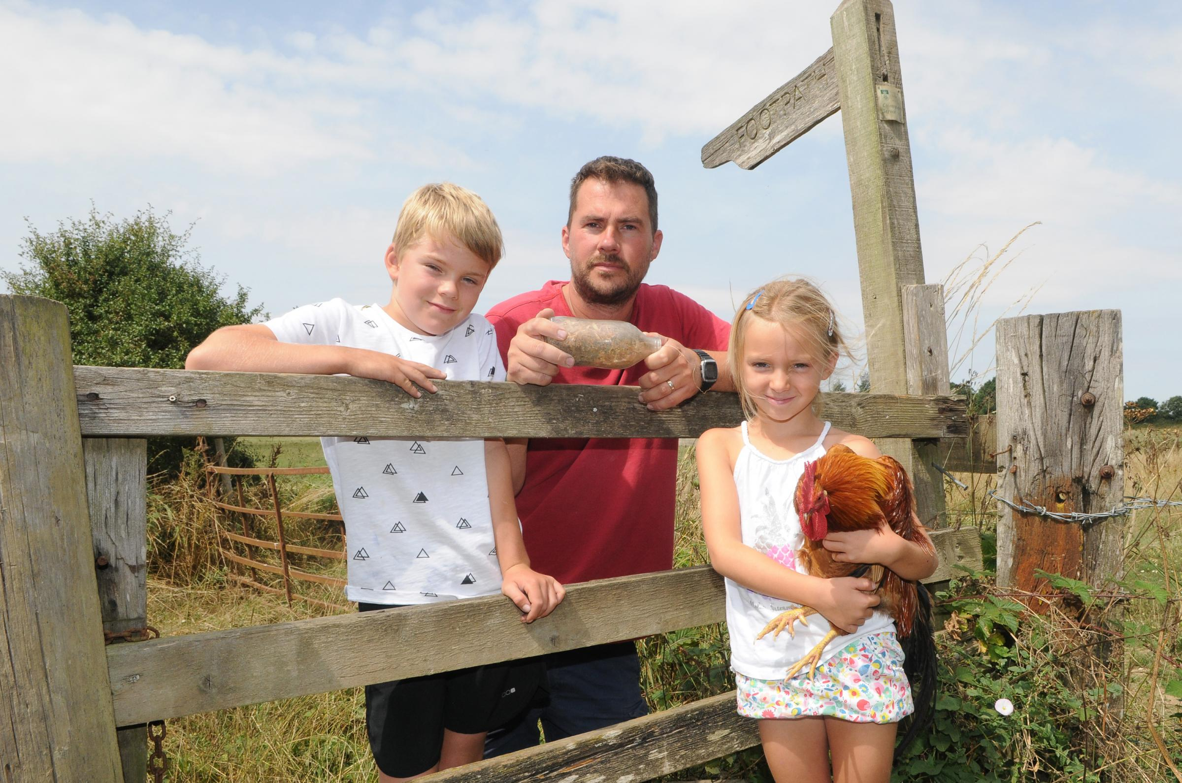 Graham Witt with son Alister, daughter Violet and rooster Goldie at Midgham Farm