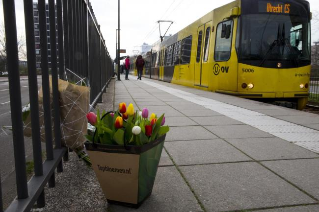 A tram passes flowers at the site of the shooting