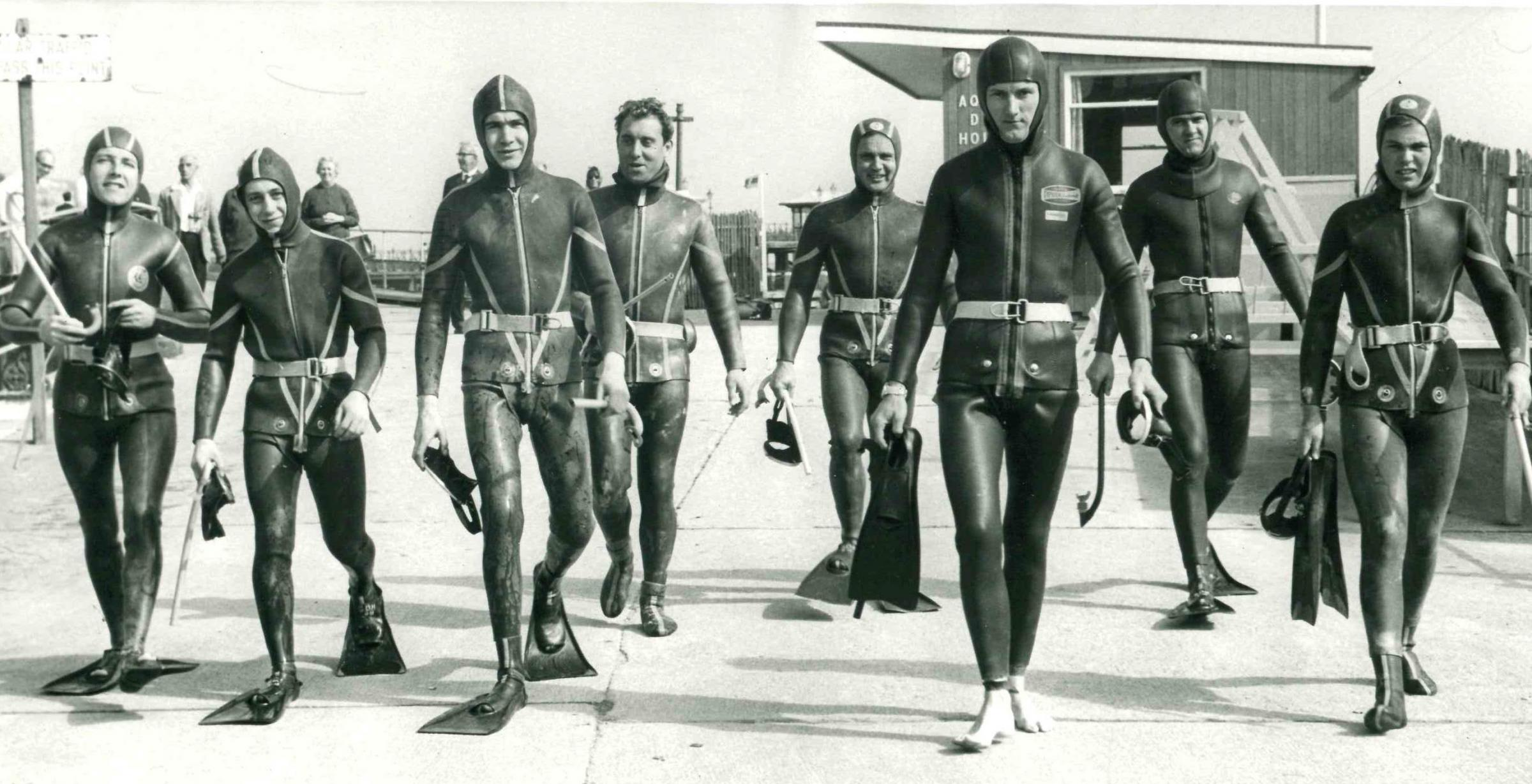An instructor from the Aqualung Diving Holidays School leads his frogmen pupils to their underwater classroom at Swanage Bay in September 1966. The classes were run by former Navy divers.